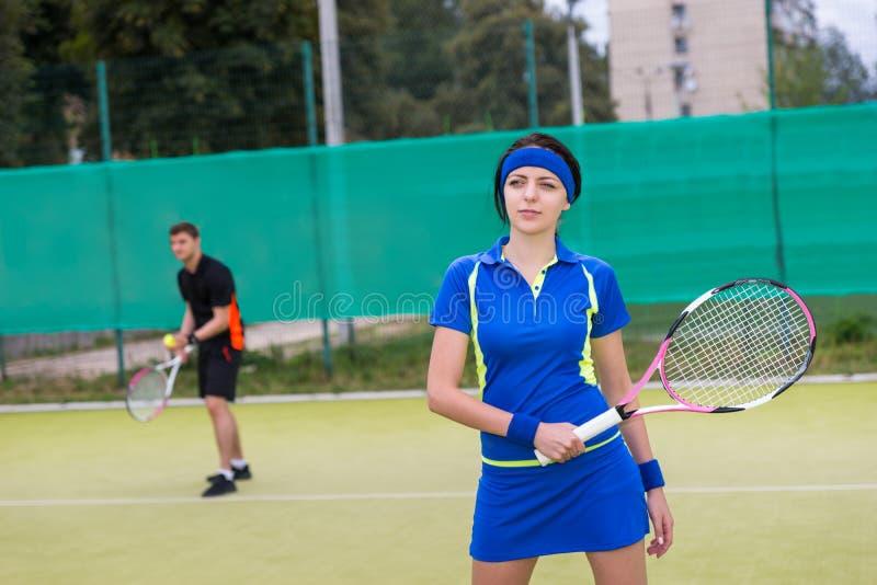 O retrato dos jogadores de tênis fêmeas e masculinos que jogam dobros excede imagem de stock royalty free