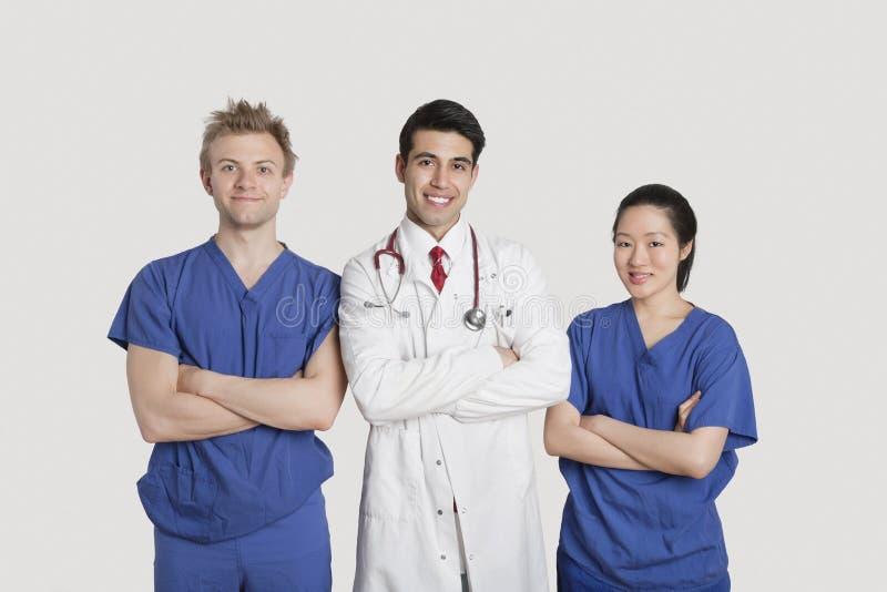 O retrato dos multi profissionais étnicos dos cuidados médicos que estão com braços cruzou-se sobre o fundo cinzento foto de stock