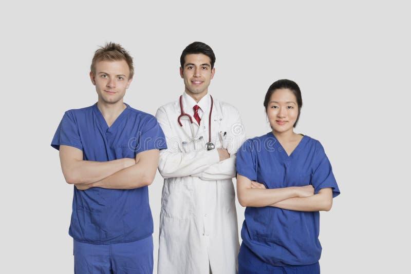 O retrato dos trabalhadores diversos dos cuidados médicos que estão com mãos dobrou o fundo cinzento imagens de stock royalty free