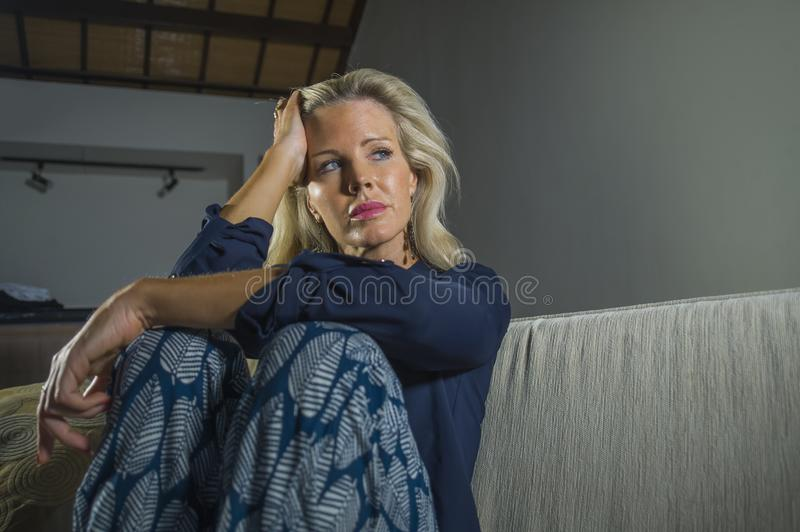 O retrato dramático do estilo de vida da mulher atrativa e triste que sente frustrada e ansiosa sentando em casa o sofá do sofá c fotografia de stock