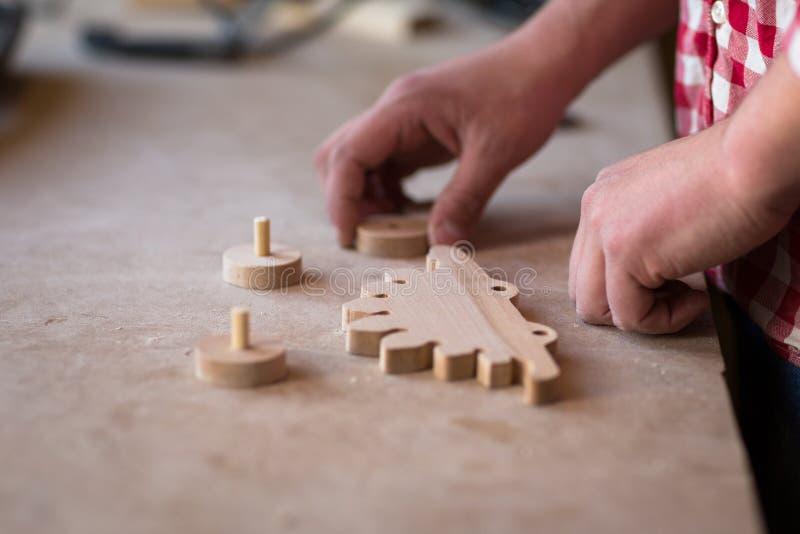 O retrato entrega a carpinteiro o brinquedo de madeira do dinossauro da roda do elemento em foto de stock royalty free