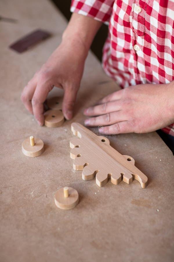 O retrato entrega a carpinteiro o brinquedo de madeira do dinossauro da roda do elemento em fotos de stock royalty free