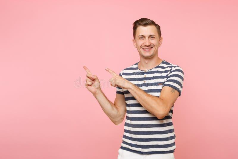 O retrato excitou o t-shirt listrado vestindo de sorriso do homem novo que aponta os indicadores de lado no espaço da cópia isola fotos de stock