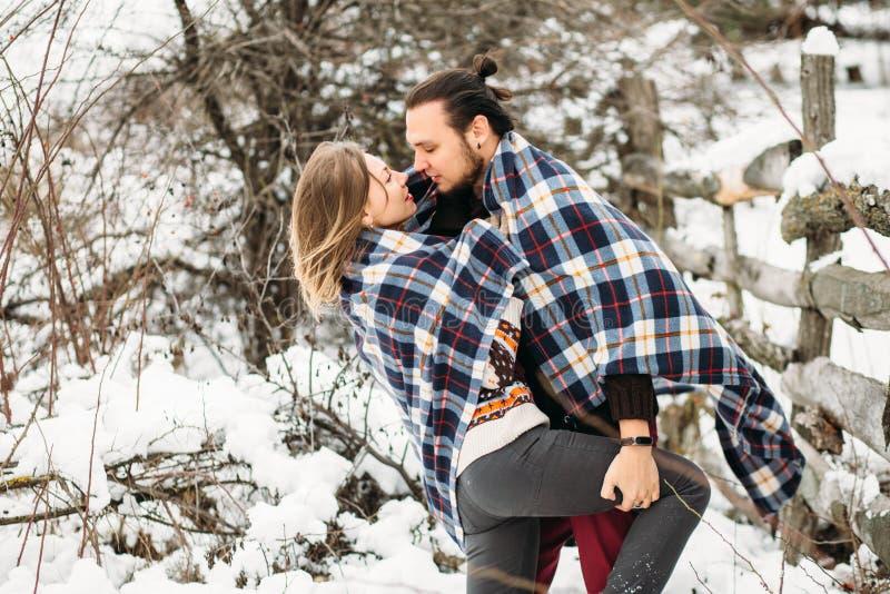 O retrato exterior da forma de pares sensuais novos no inverno frio resiste Amor e beijo fotos de stock