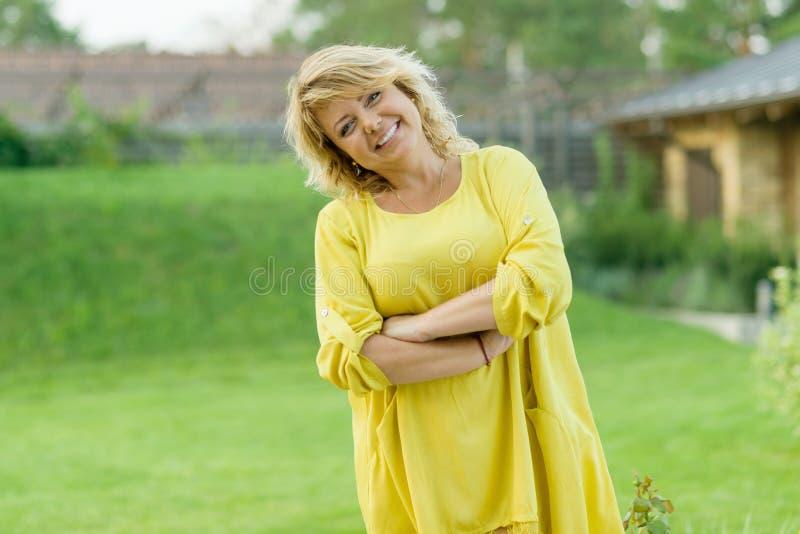 O retrato exterior da mulher de meia idade madura positiva, fêmea com braços cruzou-se, sorriso bonito, jardim do fundo imagem de stock