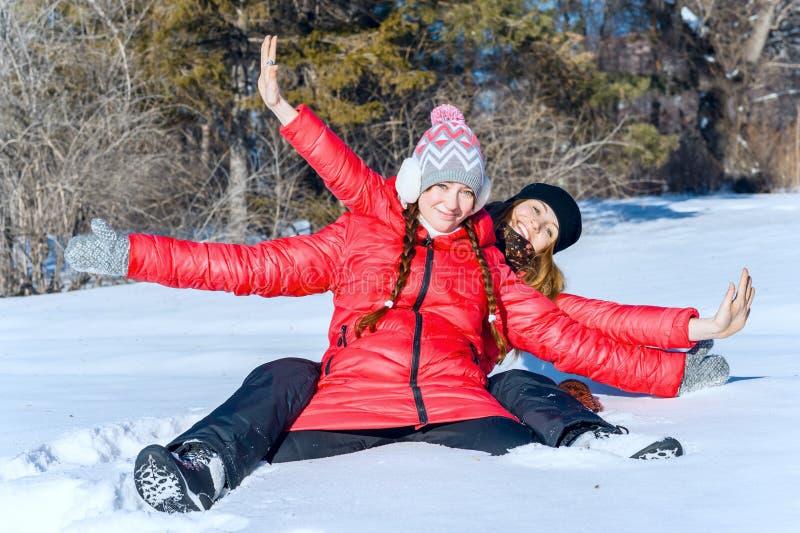 O retrato exterior de duas meninas tem o divertimento e aprecia a neve fresca em um dia de inverno bonito no parque do inverno fotografia de stock