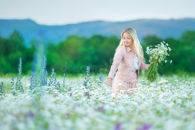 O retrato exterior de um meio bonito envelheceu a mulher loura menina 'sexy' atrativa em um campo com estrados das flores imagens de stock