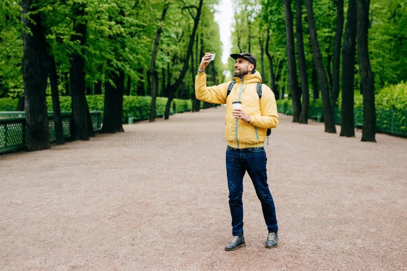 O retrato exterior do turista considerável novo vestiu-se na roupa à moda que mantém a trouxa e o café afastado que levantam na c fotografia de stock royalty free