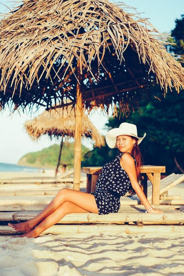 O retrato feliz da menina bonita nova com o chapéu no bambu sunbed durante o por do sol na praia imagem de stock
