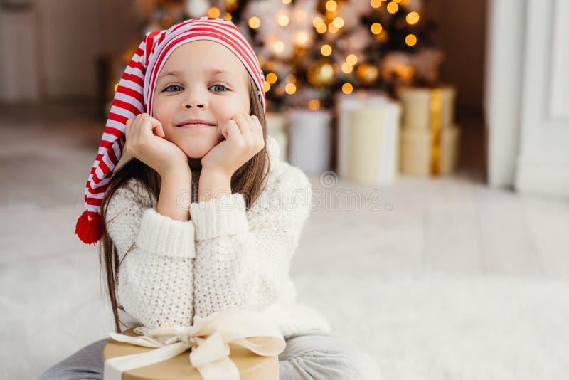 O retrato horizontal da criança pequena adorável, inclina-se na sagacidade das mãos imagem de stock royalty free