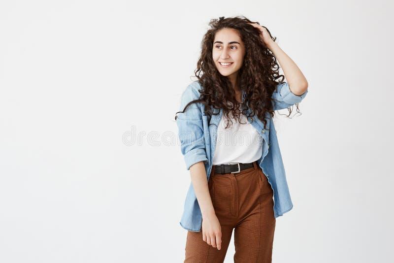 O retrato horizontal da menina bonita bonita com sorrisos atraentes da aparência felizmente, veste seu cabelo ondulado longo imagens de stock royalty free