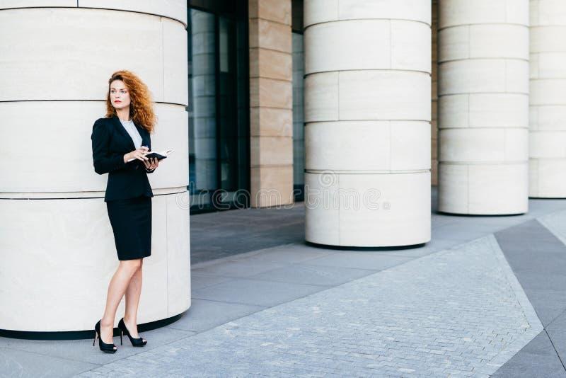 O retrato horizontal da mulher de negócios bonita vestiu-se na roupa formal e em sapatas pretas com os saltos altos, guardando o  imagem de stock royalty free
