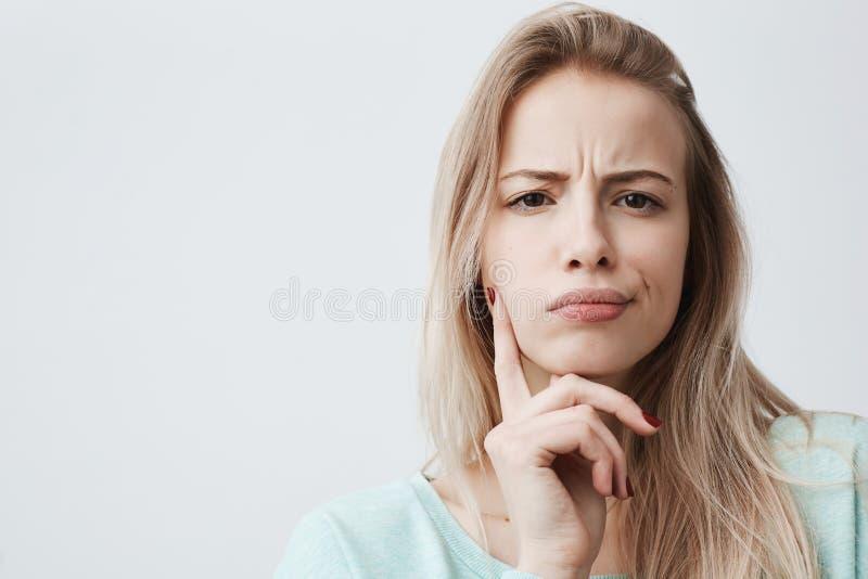 O retrato horizontal da mulher desagradada com cabelo louro tem a expressão indignante da cara, olha de sobrancelhas franzidas as fotografia de stock royalty free