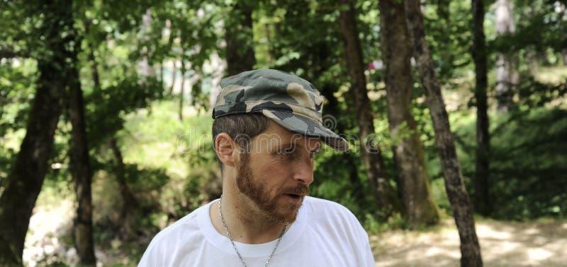 O retrato horizontal do ar livre do homem novo do caminhante feliz com barba vermelha, sente bom após a caminhada no homem farpad imagens de stock