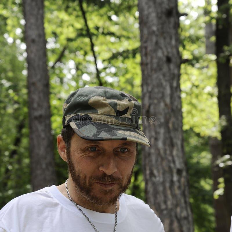 O retrato horizontal do ar livre do homem novo do caminhante feliz com barba vermelha, sente bom após a caminhada no homem farpad fotos de stock royalty free