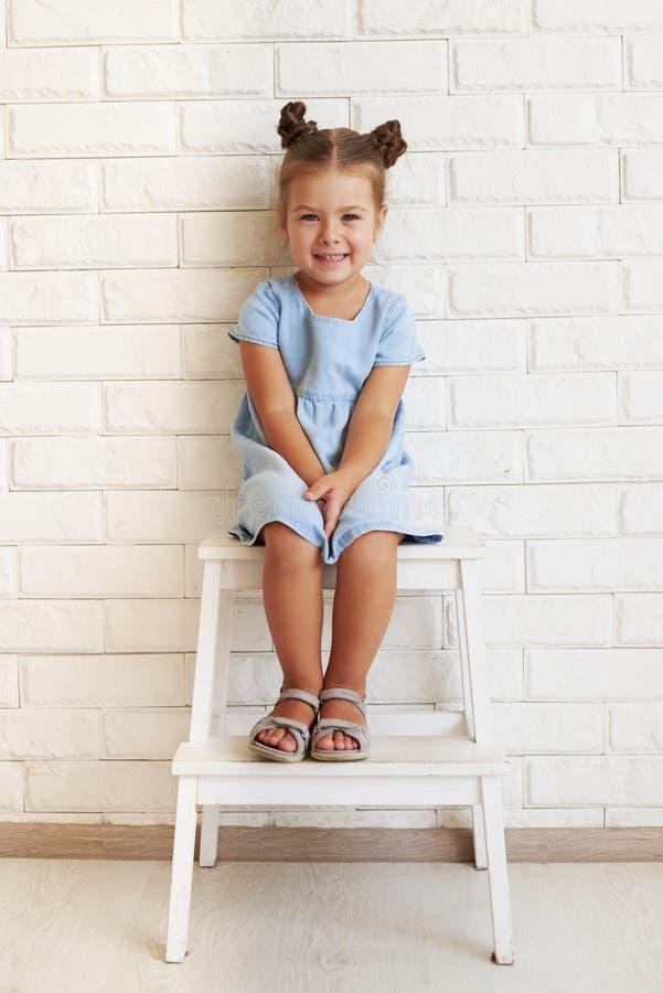 O retrato horizontal do close-up da menina pequena de sorriso deleitada senta-se fotografia de stock
