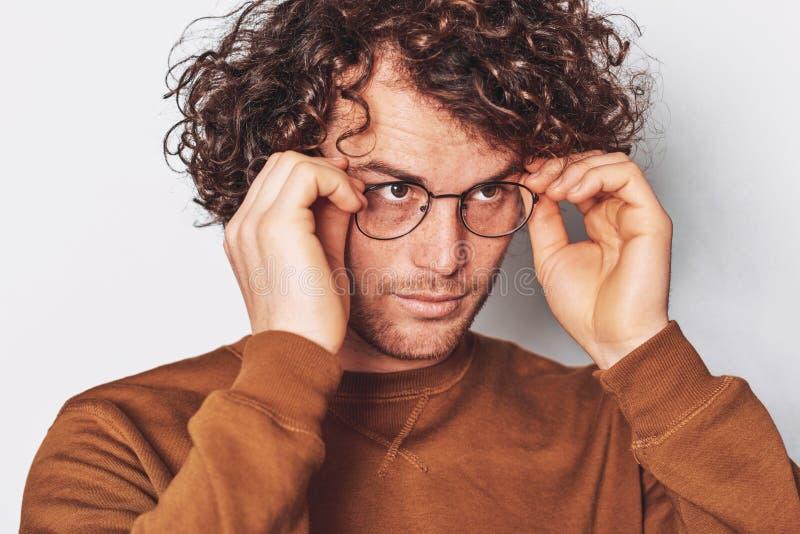 O retrato horizontal do close up do homem novo sério com cabelo encaracolado, veste os espetáculos na moda redondos, olhando em u imagem de stock