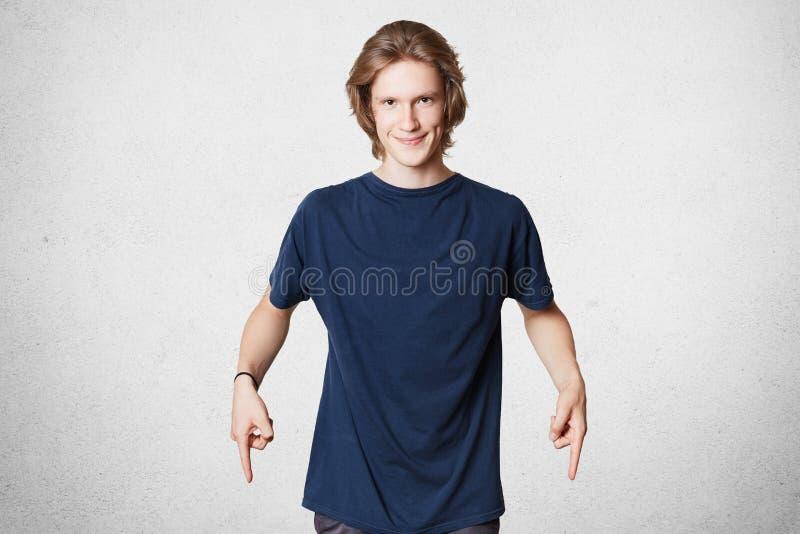 O retrato horizontal do homem bonito contente com penteado à moda, vestido ocasionalmente, indictes com indicadores para baixo, a fotografia de stock royalty free