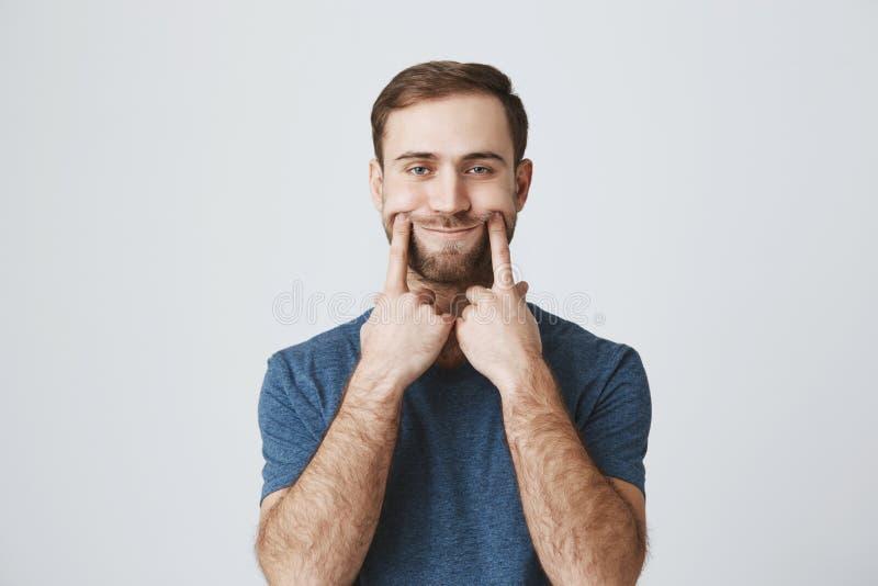 O retrato horizontal do homem descontentado e desagradado com barba vestiu-se ocasionalmente, olhando a câmera com seus olhos azu fotos de stock