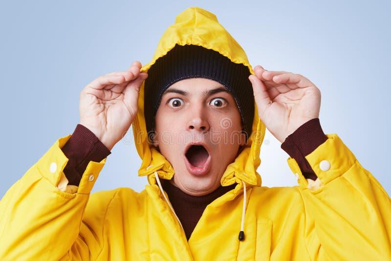 O retrato horizontal do homem embotado chocado veste a capa de chuva amarela, capa e o chapéu, olhares fora da janela, vê a chuva fotos de stock