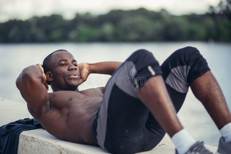 O retrato lateral de um homem negro que novo fazer se senta levanta imagem de stock royalty free