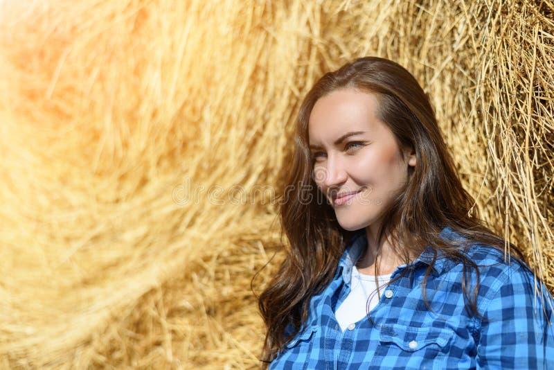 O retrato lateral de uma jovem mulher de sorriso que está de inclinação em um monte de feno em um azul prendeu a camisa do ` s do foto de stock royalty free