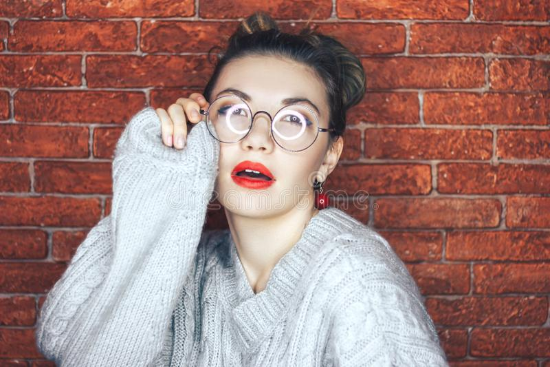 O retrato maravilhoso da menina encantador bonito com olhos bonitos e os vidros redondos com sua boca abrem levemente em um casac foto de stock royalty free