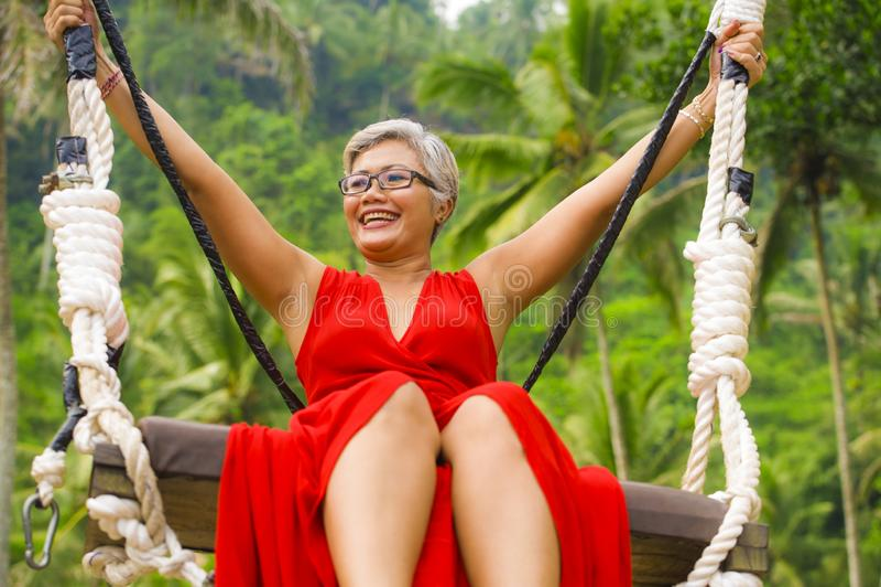 O retrato natural do estilo de vida do meio feliz atrativo envelheceu 40s - mulher 50s asi?tica com cabelo cinzento e equita??o v foto de stock