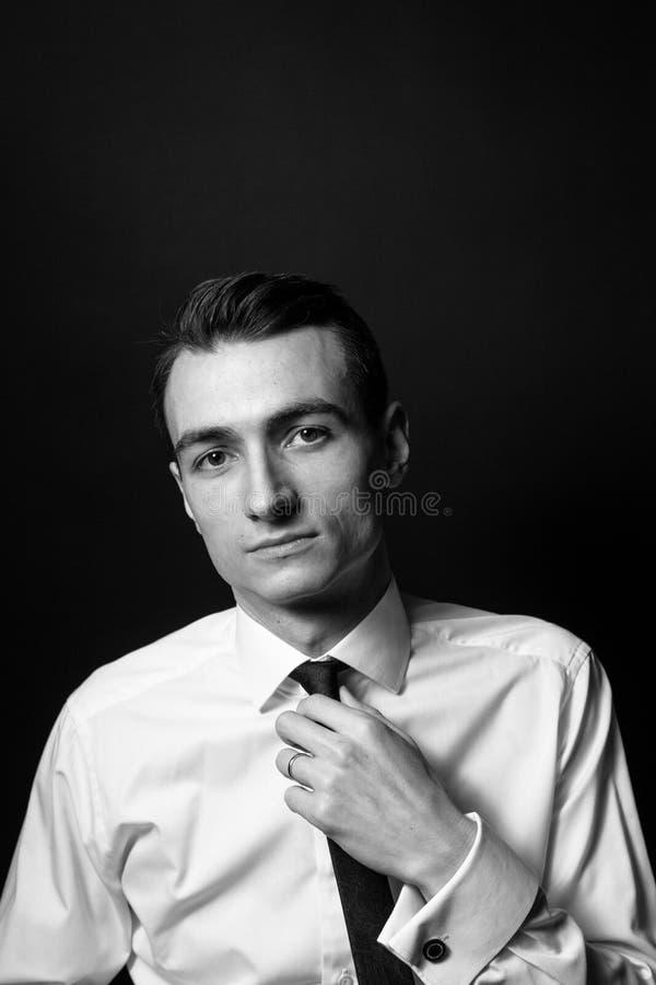 O retrato preto e branco de um homem novo em uma camisa, ajusta seu laço fotografia de stock