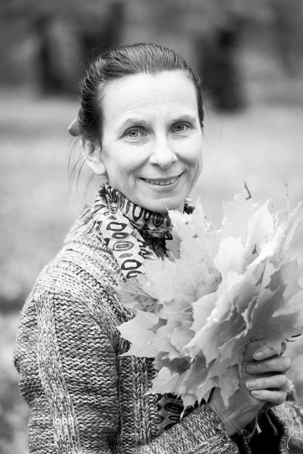 O retrato preto e branco de uma mulher caucasiano adulta de sorriso está escolhendo as folhas de bordo amarelas no outono fotografia de stock royalty free