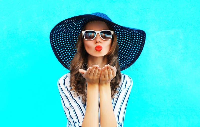 O retrato que da forma a mulher bonita com bordos vermelhos é envia um beijo do ar no chapéu do verão da palha sobre o azul color foto de stock royalty free