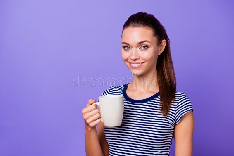 O retrato que encanta o cheiro quente da bebida listrada milenar agradável da mão da posse do t-shirt da senhora sente o independ imagem de stock royalty free