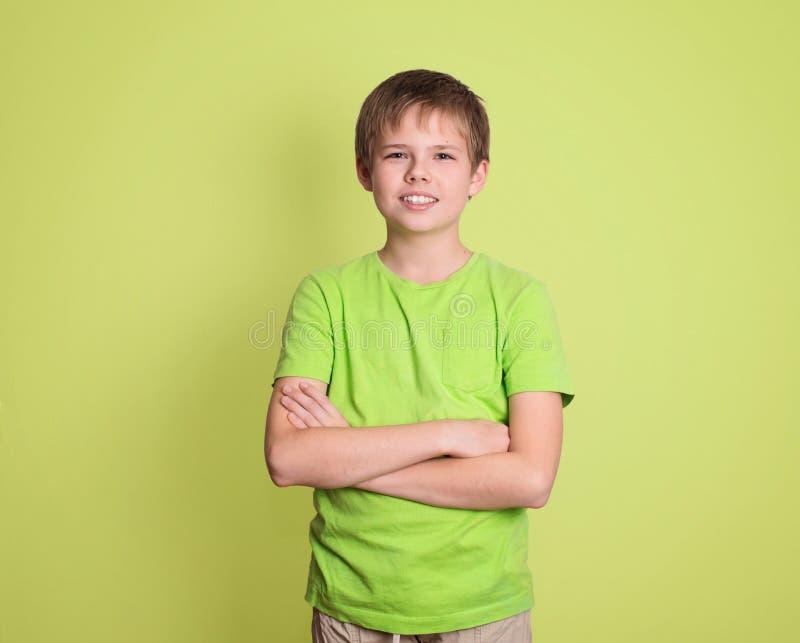 O retrato seguro do menino do preteen com braços cruzou-se isolado no gre imagens de stock