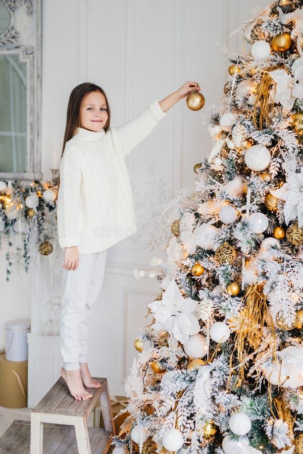 O retrato vertical da criança fêmea está perto da árvore do ano novo, HOL foto de stock royalty free