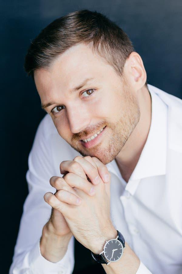 O retrato vertical do homem não barbeado alegre considerável com sorriso amigável, mantém as palmas pressionadas junto sob o quei foto de stock