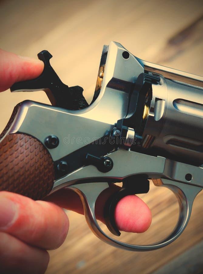 O revólver com o martelo armou em sua mão imagens de stock