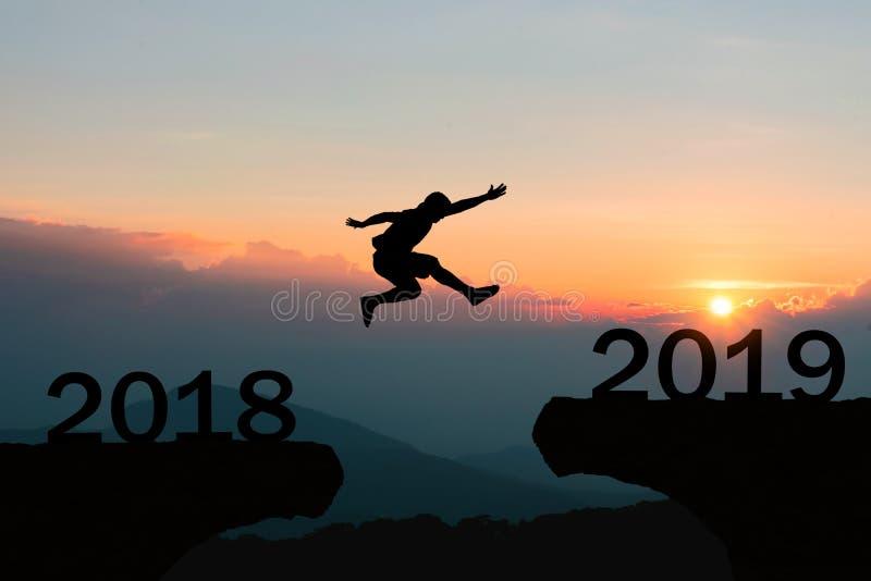 O revestimento da mulher que viaja em homens sunHappy de um ano novo 2019 da manhã fria salta sobre montanhas da silhueta imagens de stock