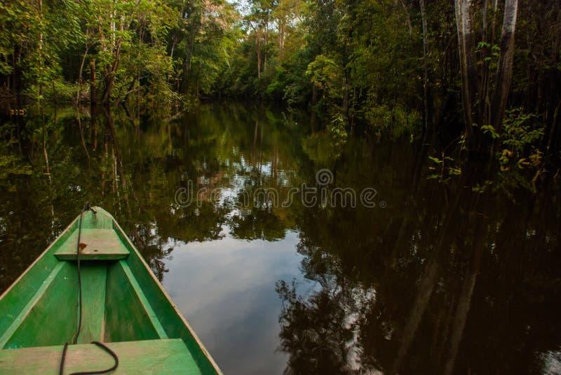 O Rio Amazonas, Manaus, Amazonas, Brasil: Barco de madeira que flutua no Rio Amazonas nas marés da selva das Amazonas fotografia de stock royalty free