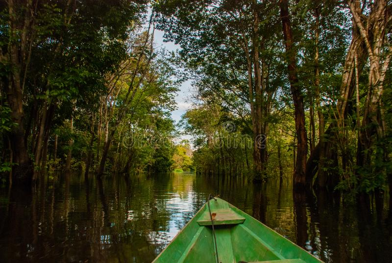O Rio Amazonas, Manaus, Amazonas, Brasil: Barco de madeira que flutua no Rio Amazonas nas marés da selva das Amazonas imagem de stock
