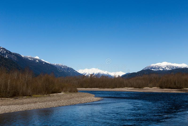 O rio de Squamish e as montanhas neve-repicadas da costa no parque provincial de Brackendale Eagles foto de stock
