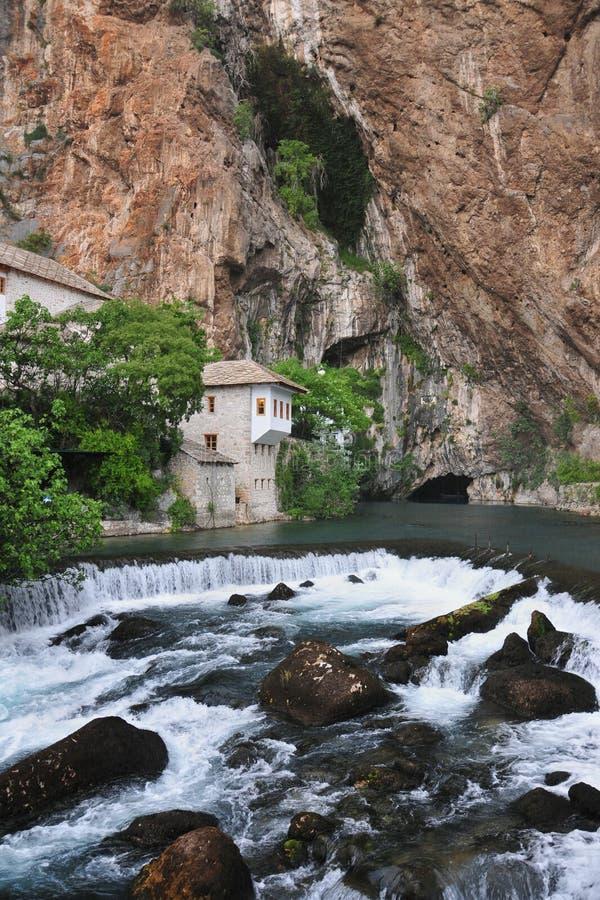 O rio do Buna com uma cachoeira que flui fora da caverna, assim como o tekkia - uma casa antiga do dervixe, monges, Blagaj imagens de stock royalty free