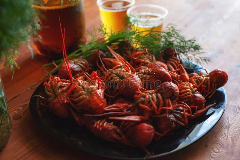 O rio ferveu as lagostas, cozinhadas e servidas em uma tabela para a cerveja foto de stock