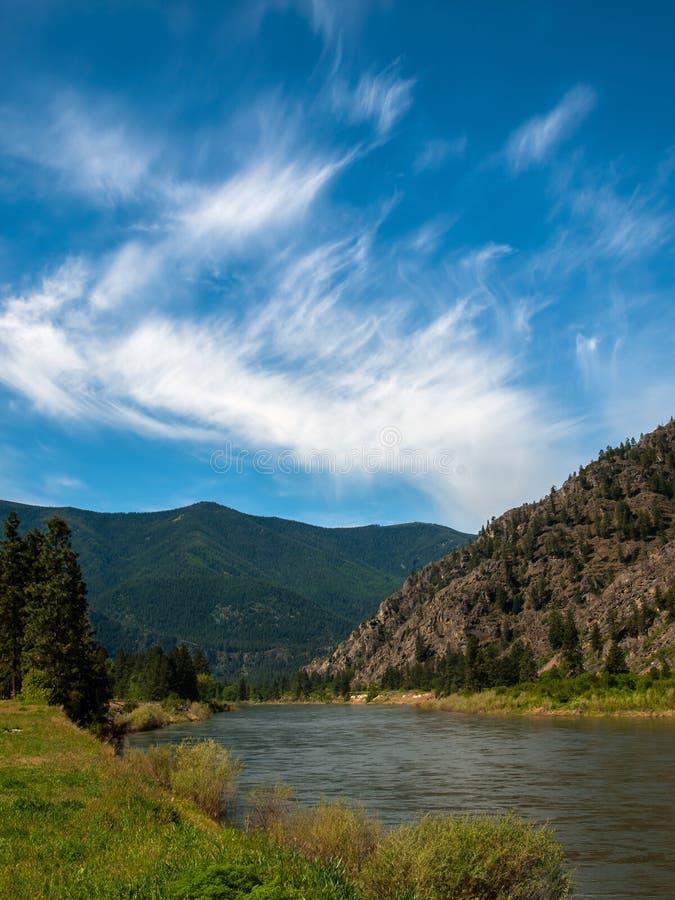 O rio largo da montanha corta um vale fotografia de stock
