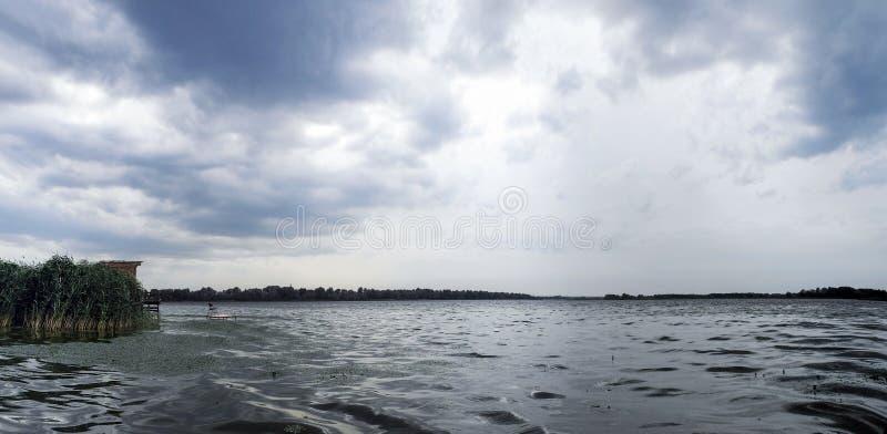 O rio largo em um dia nebuloso cinzento Ponte acolhedor para pescar Ondas de prata na água escura imagem de stock
