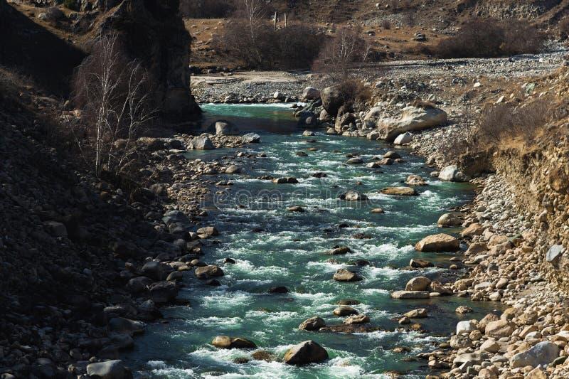 O rio tormentoso da montanha com pedras espirra e espuma com a água potável clara da cor esmeralda O conceito de natural fotos de stock royalty free