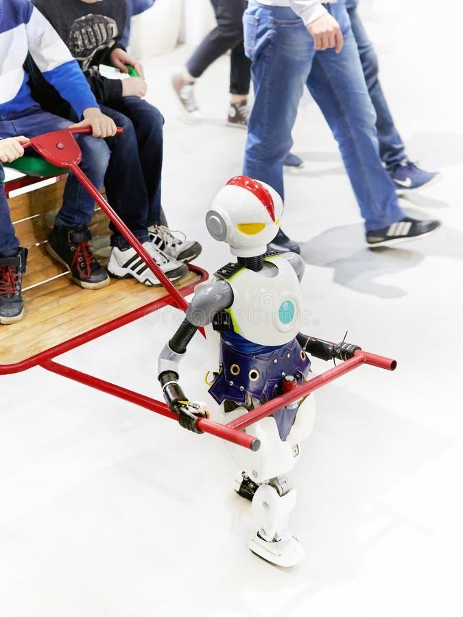 O riquexó do robô conduz crianças em um carro no fundo do ot imagem de stock