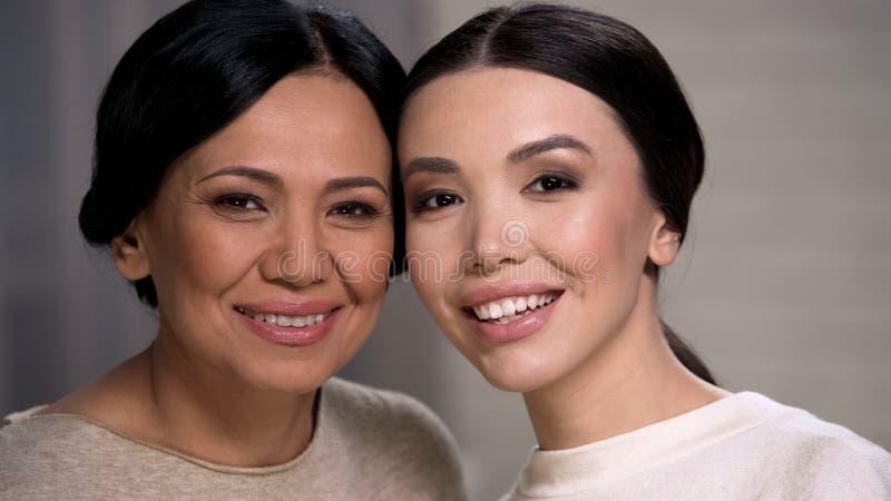 O riso asiático alegre da mãe e da filha, olhando a câmera, enfrenta o close up imagens de stock royalty free