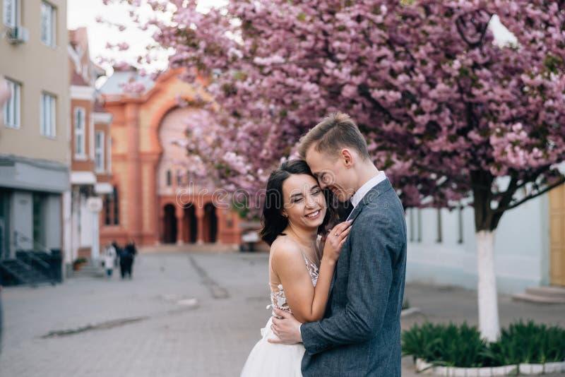 O riso dos noivos na rua Terno do vestido e do noivo de casamento imagens de stock royalty free