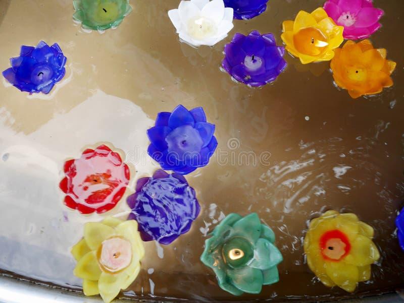 O ritual que reza a vela colorida que flutua na água para reza buddha foto de stock
