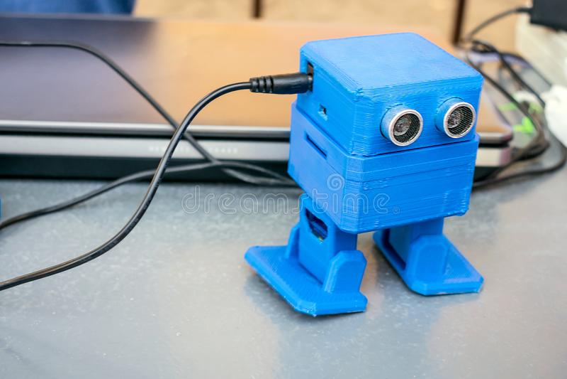 O robô azul engraçado imprimiu em uma impressora 3D Roubo automático bonito do brinquedo foto de stock